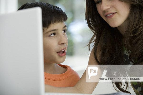 Schwester und jüngerer Bruder benutzen gemeinsam einen Laptop.