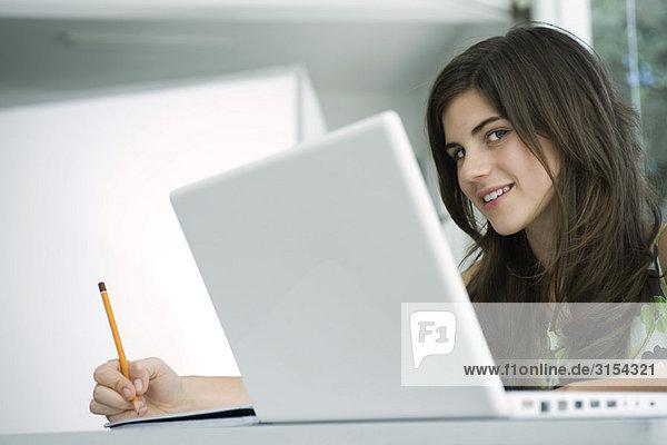 Teenager Mädchen am Schreibtisch schreiben  Laptop im Vordergrund