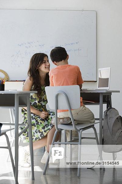 Tutorin in der Arbeit mit Grundschülern im Klassenzimmer