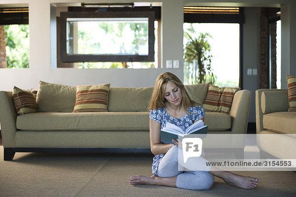 Junge Frau auf dem Wohnzimmerboden sitzend Lesebuch