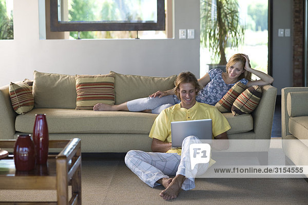 Paar im Wohnzimmer  Frau auf dem Sofa liegend  Mann auf dem Boden sitzend mit Notebook