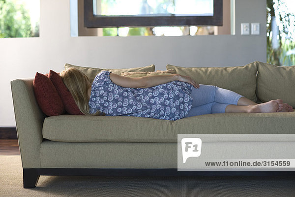 Junge Frau schläft auf dem Sofa  Rückansicht