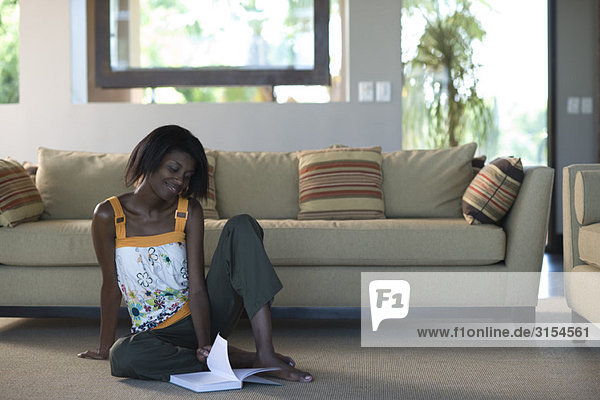 Young woman sitting on living room floor leafing through pages of book