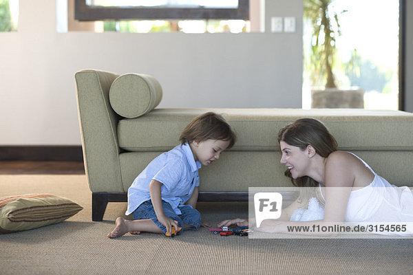 Mutter und Kind spielen mit Spielzeugautos