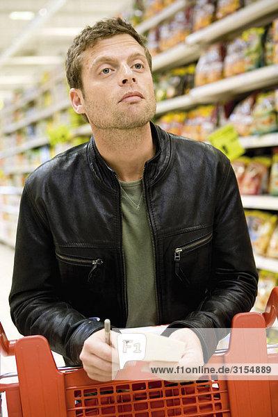 Mann im Supermarkt mit Einkaufsliste