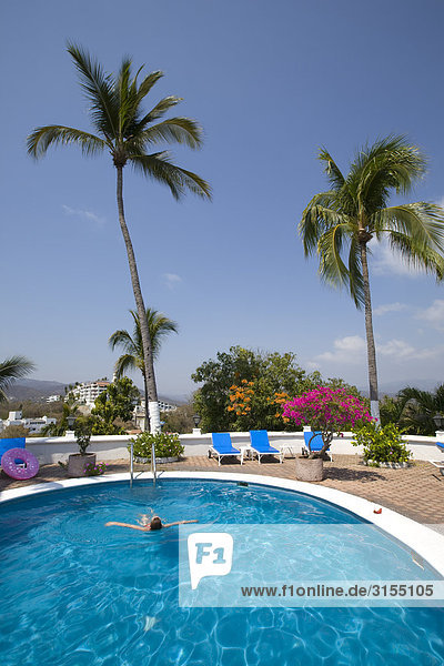 Woman swimming in pool with palm trees  Manzanillo  Jalisco  Mexico