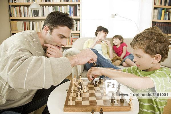 Vater und Sohn spielen von Schach