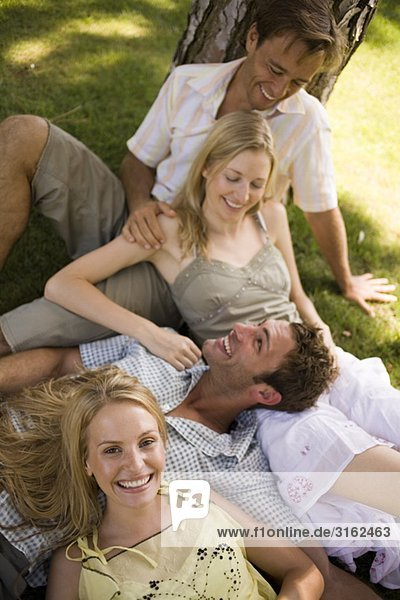 Two couples outdoors leaning on a tree trunk