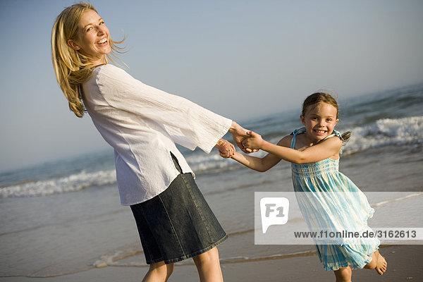 Eine Mutter und Tochter Spinnerei am Strand