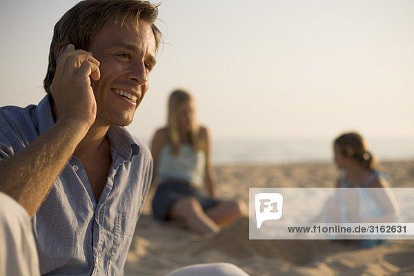 Ein Mann auf einem Cellular am Strand mit seiner Familie im Hintergrund
