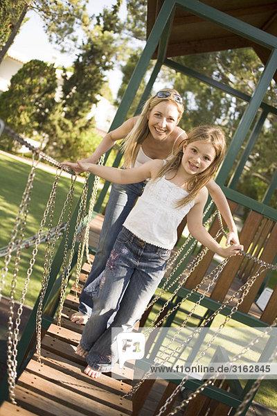 Eine Mutter und Tochter spielen auf einem Spielplatz Eine Mutter und Tochter spielen auf einem Spielplatz