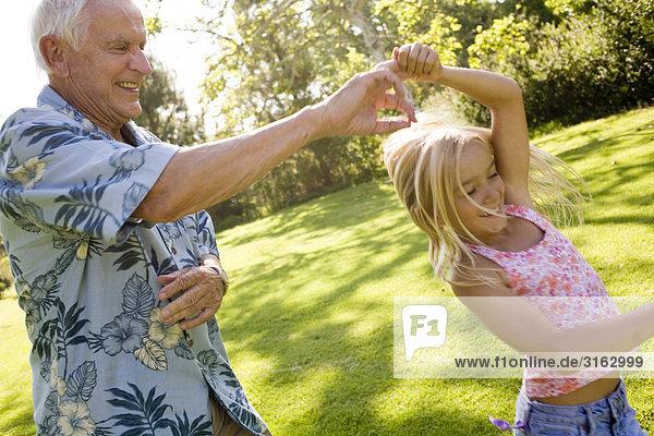 Ein Großvater mit seiner Enkelin in einem Park tanzen