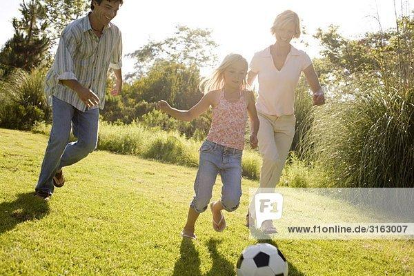Eine Familie in einem Park mit einem Fußball spielen