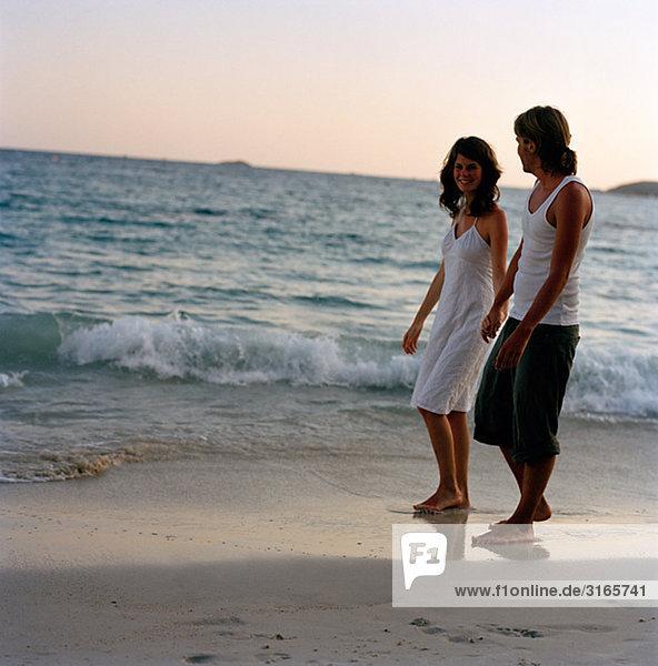 Ein junges paar gehen Hand in Hand am Strand  Thailand.