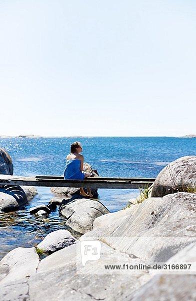 Eine Frau sitzt auf einer Landesteg Stockholmer Schären Schweden.