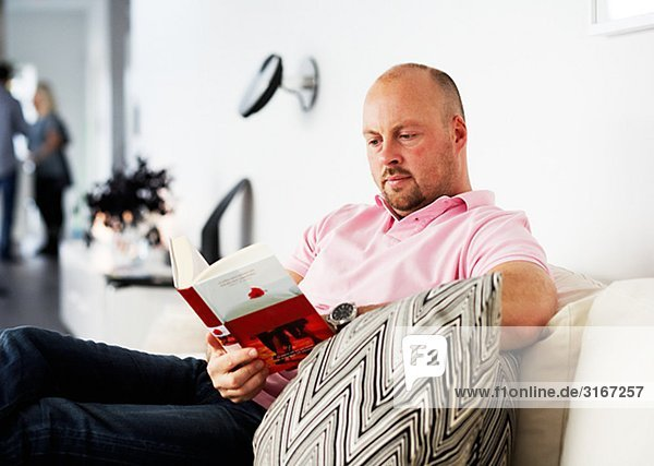 A man sitting in a couch reading a book Sweden.