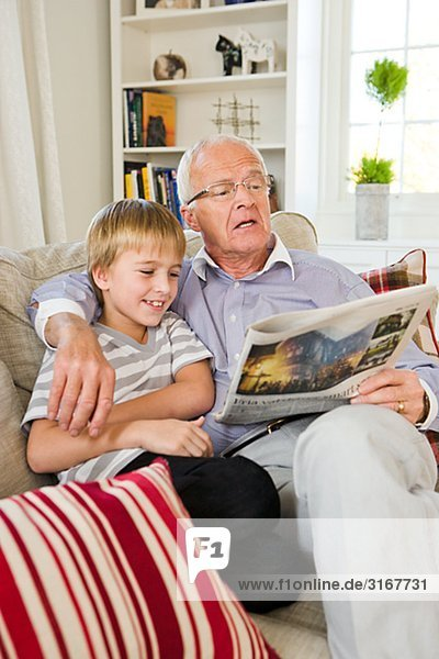 Grandfather and grandson in a sofa  reading  Sweden.