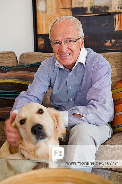 Senior man in a sofa patting a dog  Sweden.