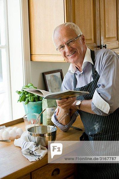älterer Mann dabei  Kochen  lesen ein Kochbuch  Schweden.