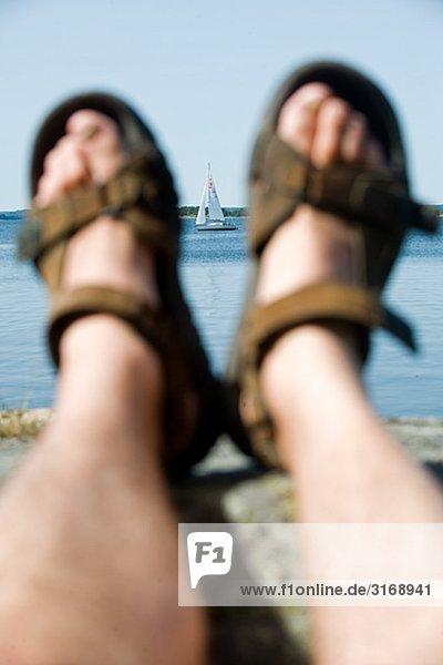 Füße mit Sandalen und ein Segelboot Schweden.