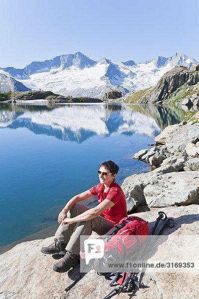 Frau an einem Bergsee sitzend  Tirol  Österreich  Erhöhte Ansicht