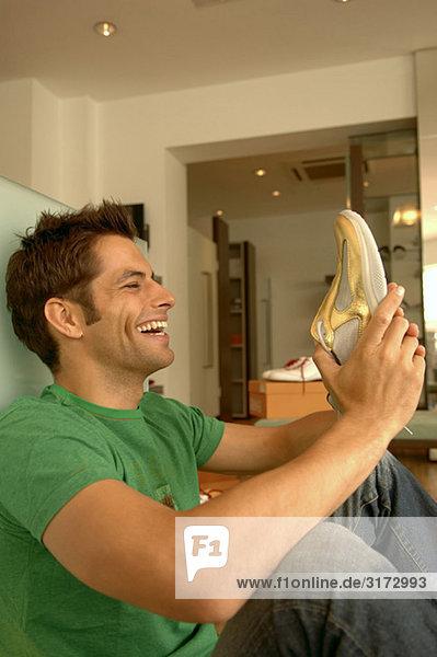 Junger dunkelhaariger Mann freut sich über den Schuh in seiner Hand - Geschäft - Laden Junger dunkelhaariger Mann freut sich über den Schuh in seiner Hand - Geschäft - Laden