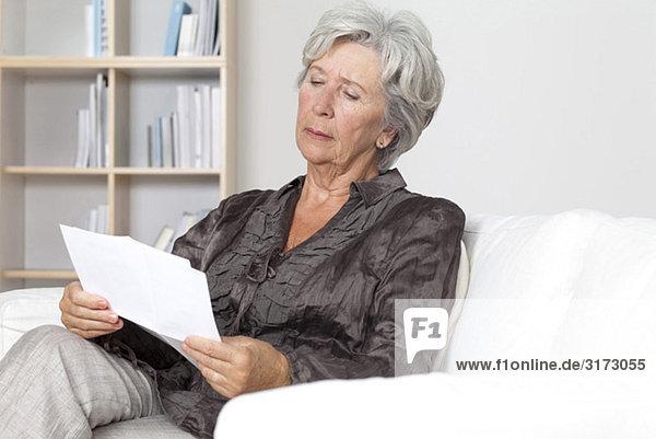 Seniorin liest ein Dokument auf der Couch Seniorin liest ein Dokument auf der Couch