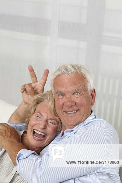 Senior couple on couch fooling around