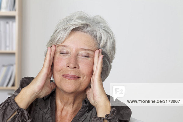 Seniorin massiert ihr Gesicht