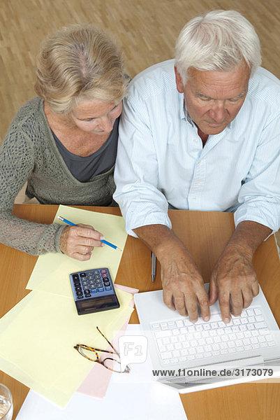 Seniorenpaar mit Laptop und Taschenrechner Seniorenpaar mit Laptop und Taschenrechner