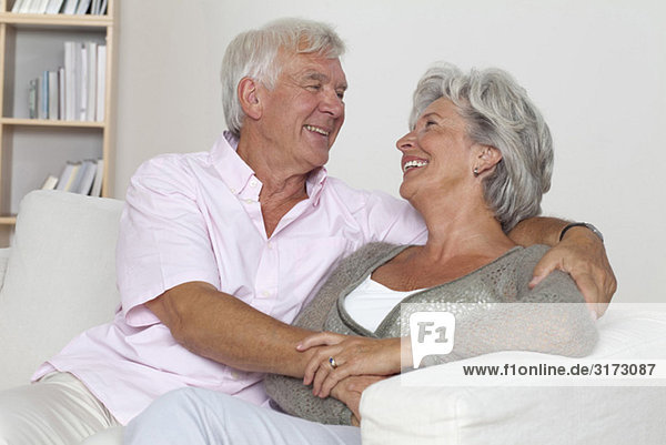 Seniorenpaar umarmt sich auf der Couch Seniorenpaar umarmt sich auf der Couch