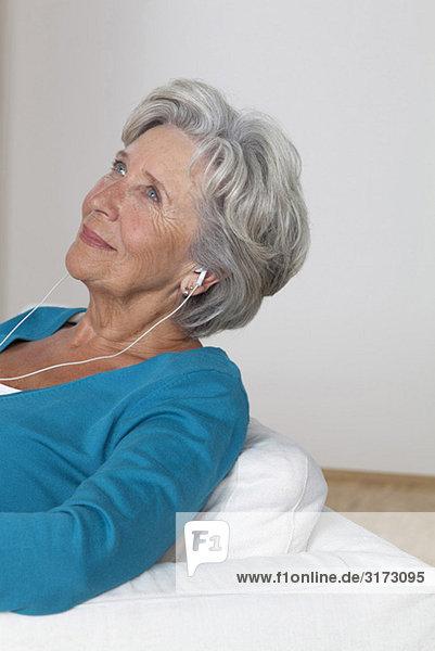 Seniorin hört Musik auf der Couch Seniorin hört Musik auf der Couch