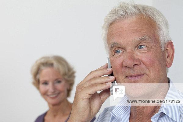 Senior telefoniert mit Frau im Hintergrund Senior telefoniert mit Frau im Hintergrund