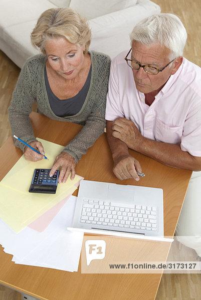 Seniorenpaar mit Laptop und Taschenrechner