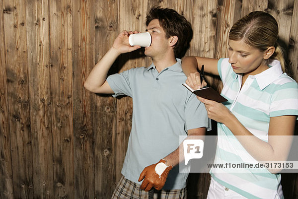 Two golf players with diary in front of wooden wall