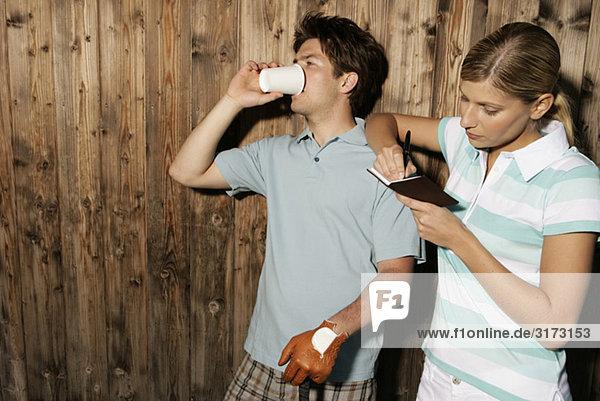 Golfer und Golferin mit Terminkalender vor Holzwand