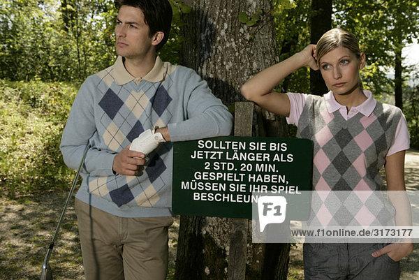 Junges Paar neben Hinweisschild auf Golfplatz