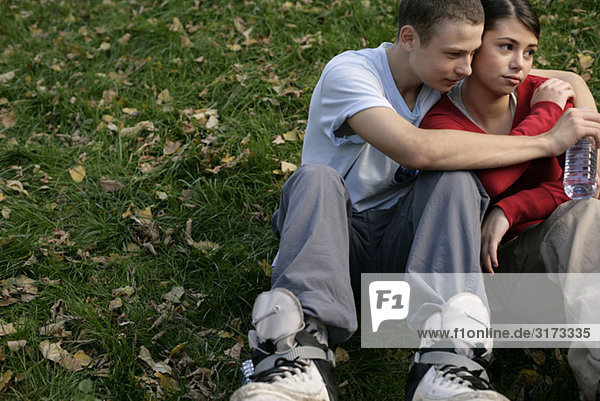 Teenage couple sitting on grass and embracing