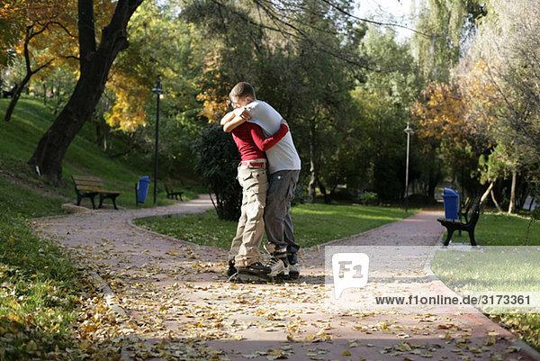 Teenagerpaar mit Inlineskates umarmt sich