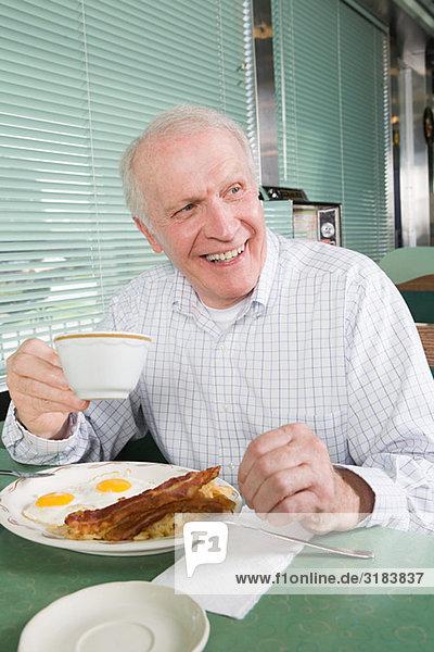 Älterer Mann  der ein gebratenes Frühstück isst