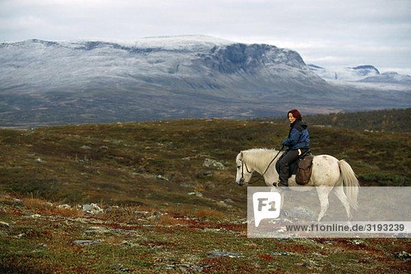 Sami Frau Fahrer auf einem Pferd in der Natur  Schweden.