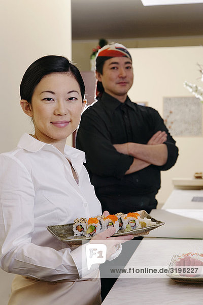 portrait of japanese waitress and chef with sushi