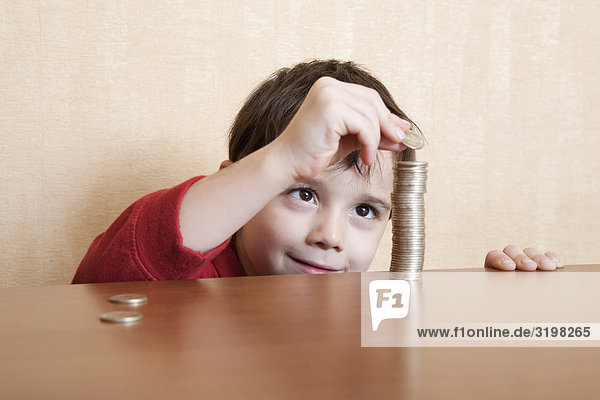 young boy making pile of coins