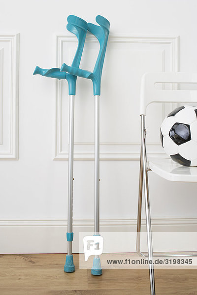 still life of crutches and football on chair