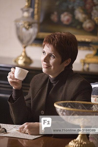 Reife Frau sitzen im Wohnzimmer Kaffeetrinken