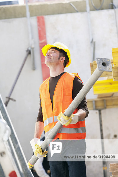 construction worker holding metal part