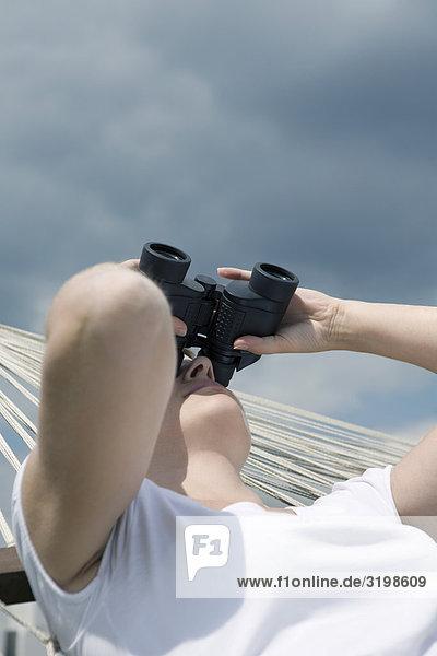 junge Frau liegen in der Hängematte beobachten den Himmel mit einem Fernglas