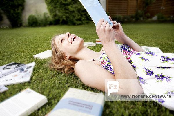 liegend liegen liegt liegendes liegender liegende daliegen junge Frau junge Frauen Buch Garten Gras vorlesen