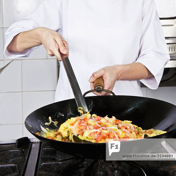 Female chef cooking food in the kitchen