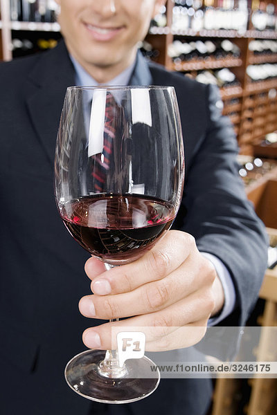 Businessman showing a wine glass in a bar